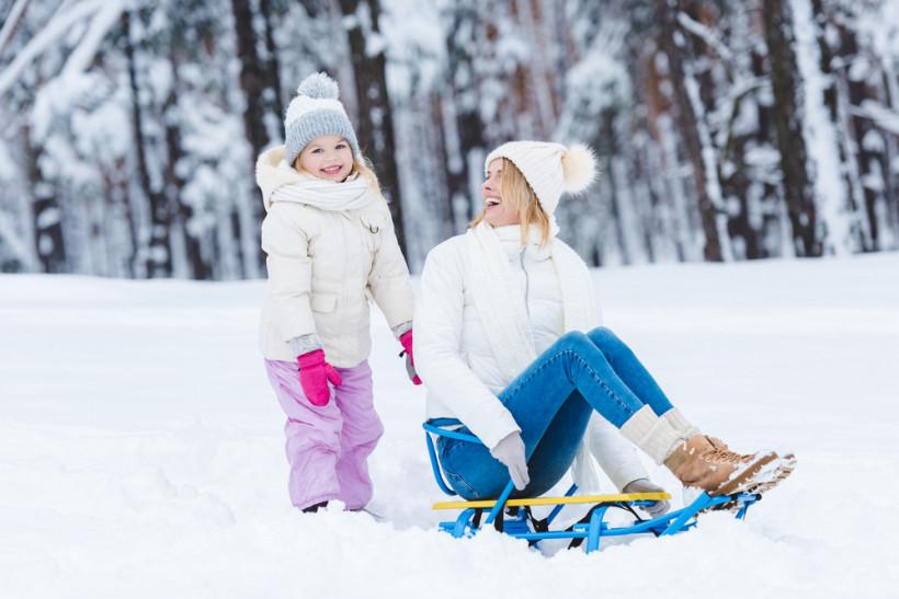 мама с дочкой катаются на санках зимой