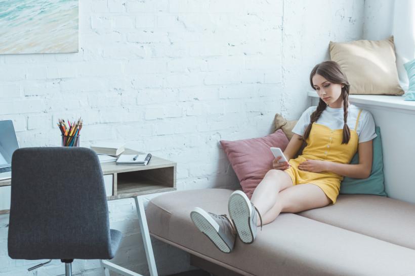 девушка подросток смотрит в смартфон