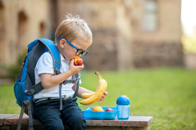 хлопчик їсть фрукти