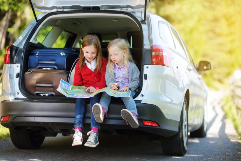 Дети в автомобиле рассматривают карты