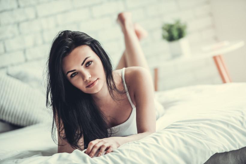 Красивая девушка лежит на кровати