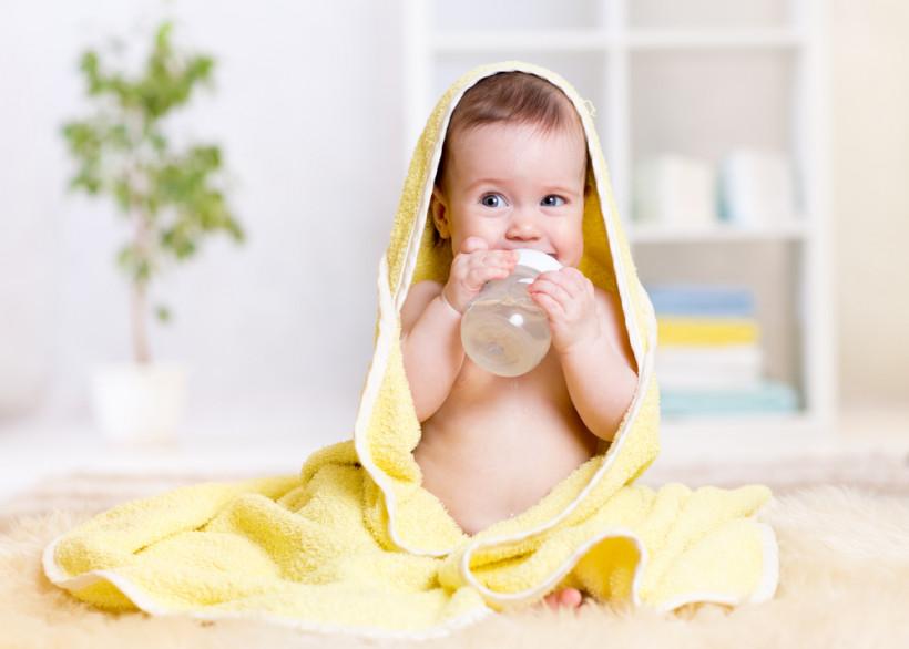 Малыш в полотенце пьет воду