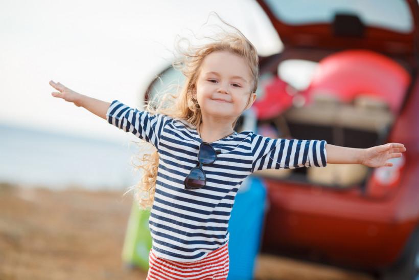 Счастливый ребенок на фоне машины
