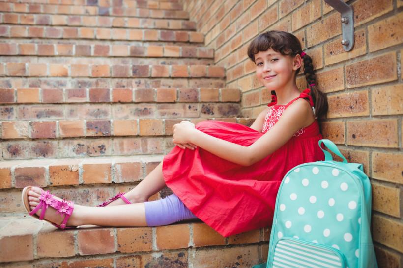 Девочка улыбается на кирпичной лестнице