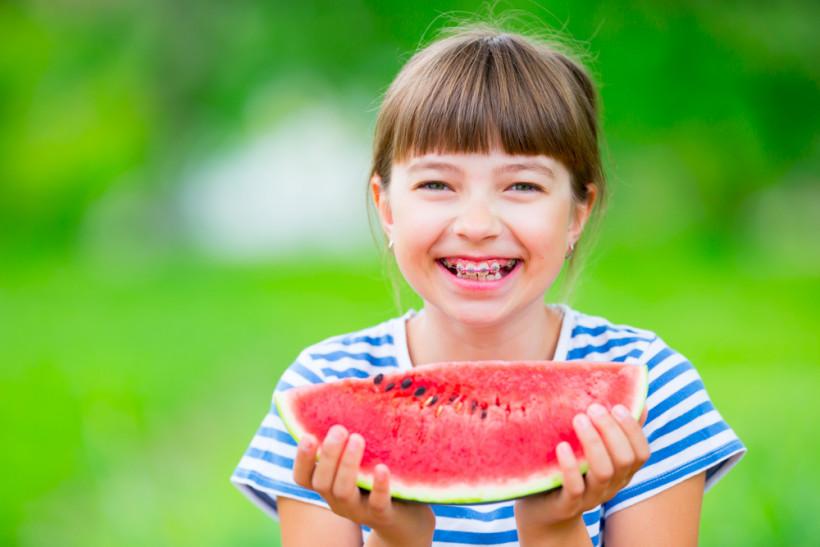 Девочка с брекетами ест арбуз