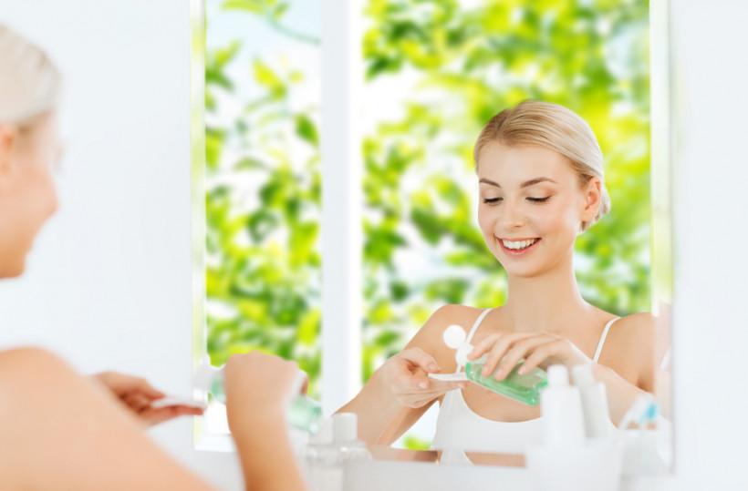 Женщина очищает лицо в ванной