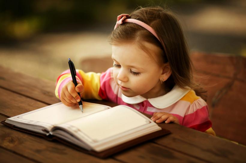 Девочка пишет ручкой