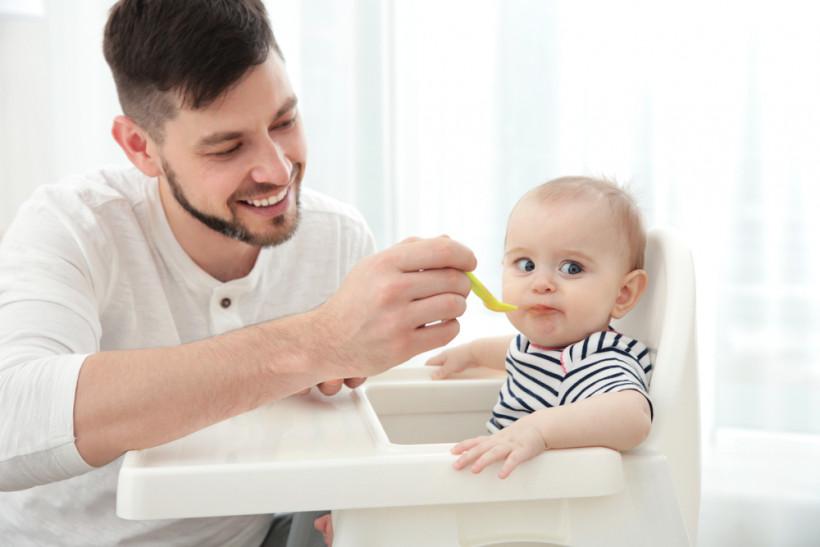 тато годує малюка