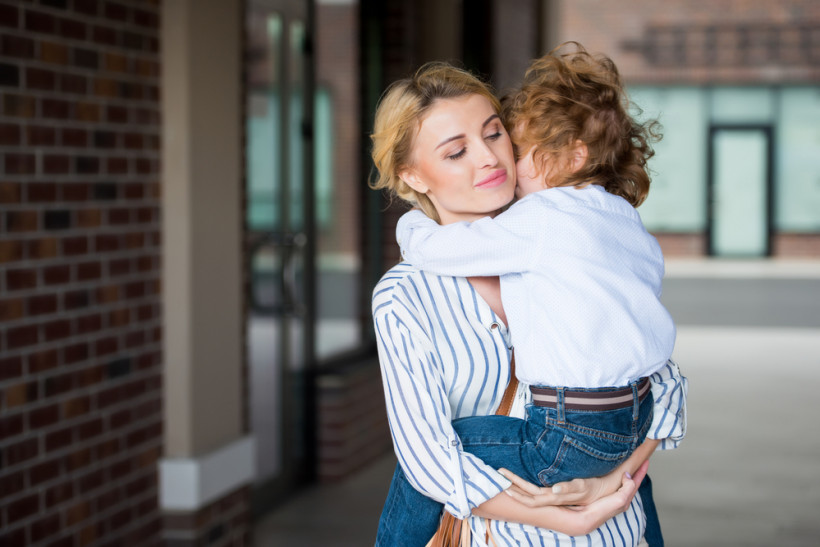 мама обнимает сына, держа на руках