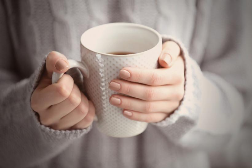 Большая чашка кофе в руках у женщины