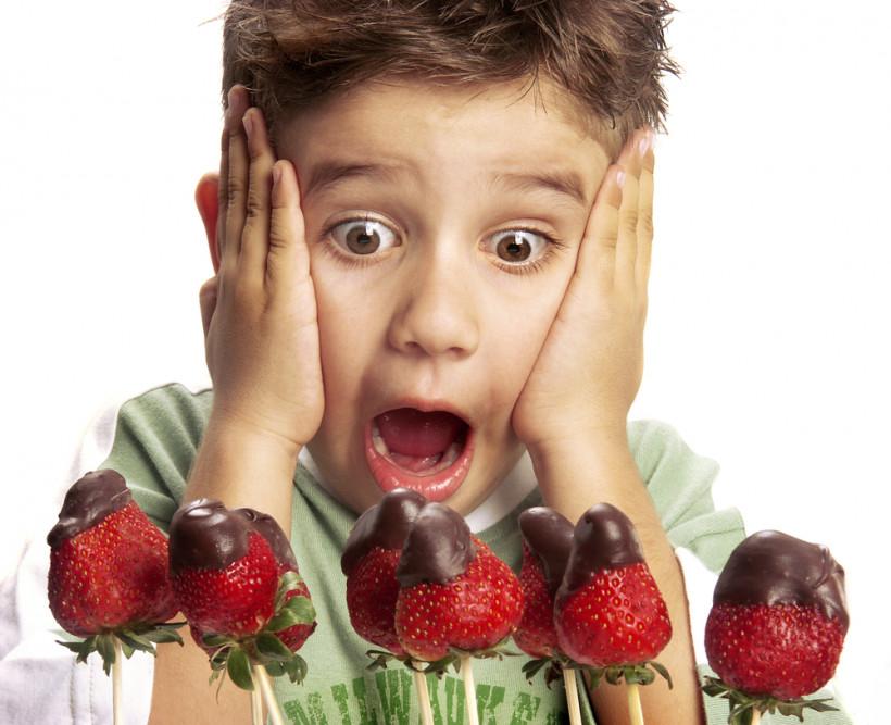 Мальчик смотрит на клубнику в шоколаде