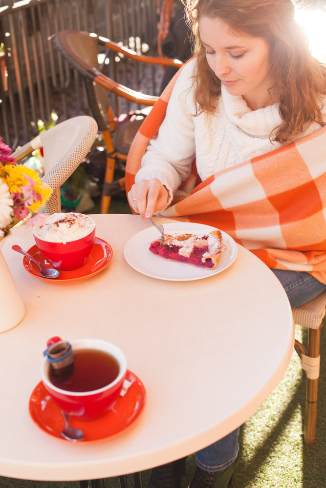 Девушка укуталась в плед и пьет кофе осенью в кафе