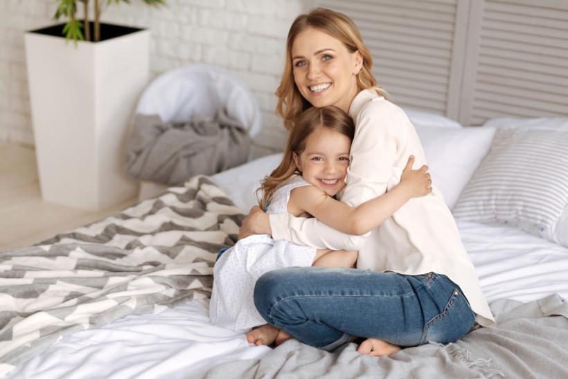 мама обнимает свою маленькую дочку