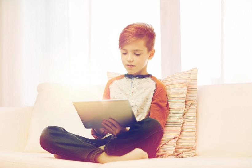 ребенок с планшетом на диване