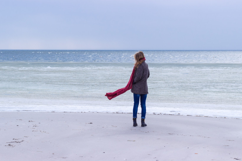 Девушка с депрессией на фоне холодного моря