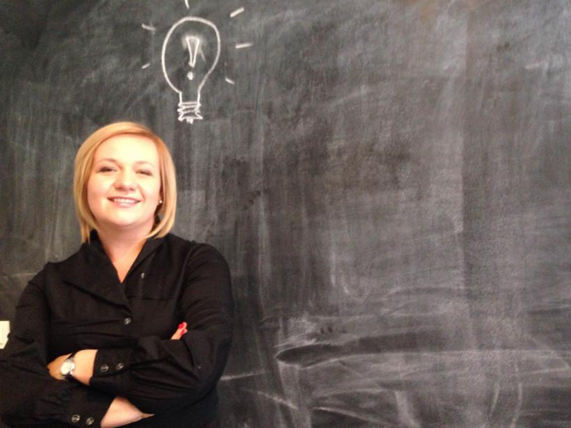 Оксана Макаренко на фоне доски с изображением лампочки