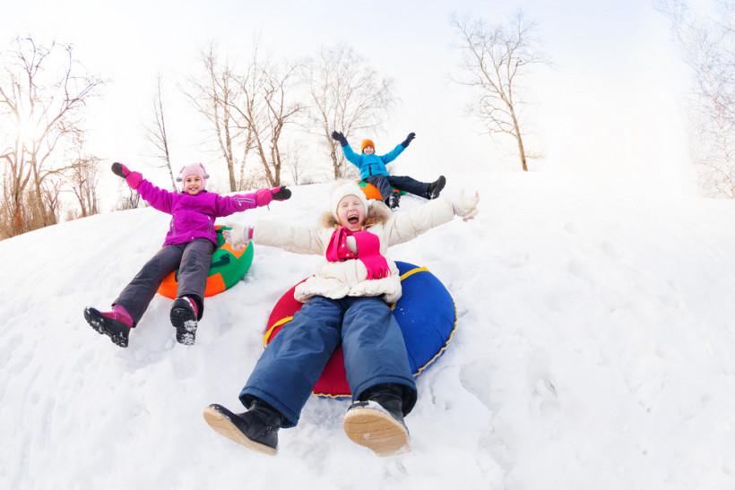 дети катаются на санках зимой