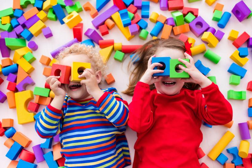 Дети играют кубиками на полу