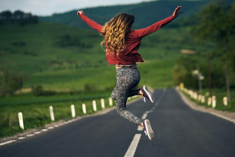 Женщина в прыжке на дороге