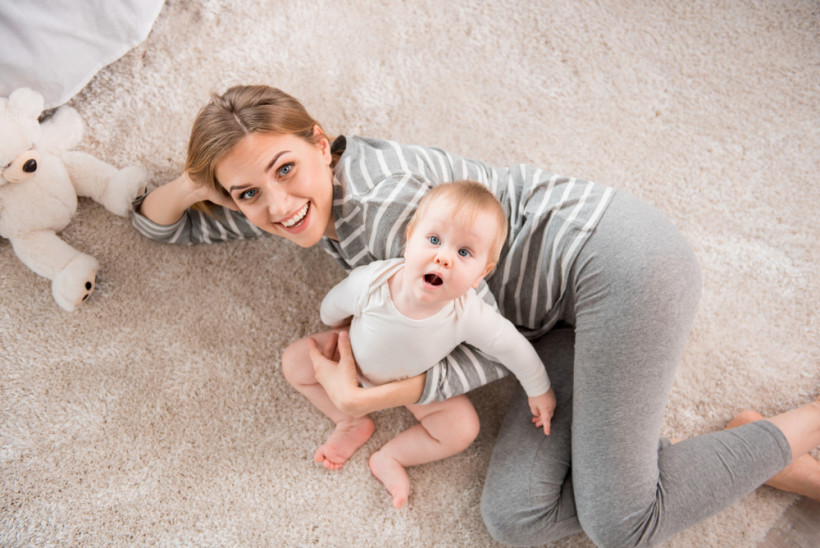 Удивленный ребенок  с мамой на полу