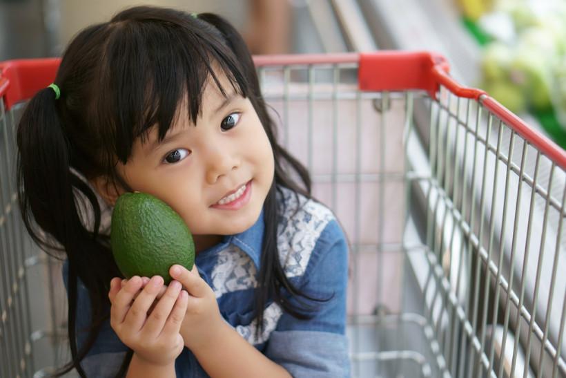 девочка держит авокадо