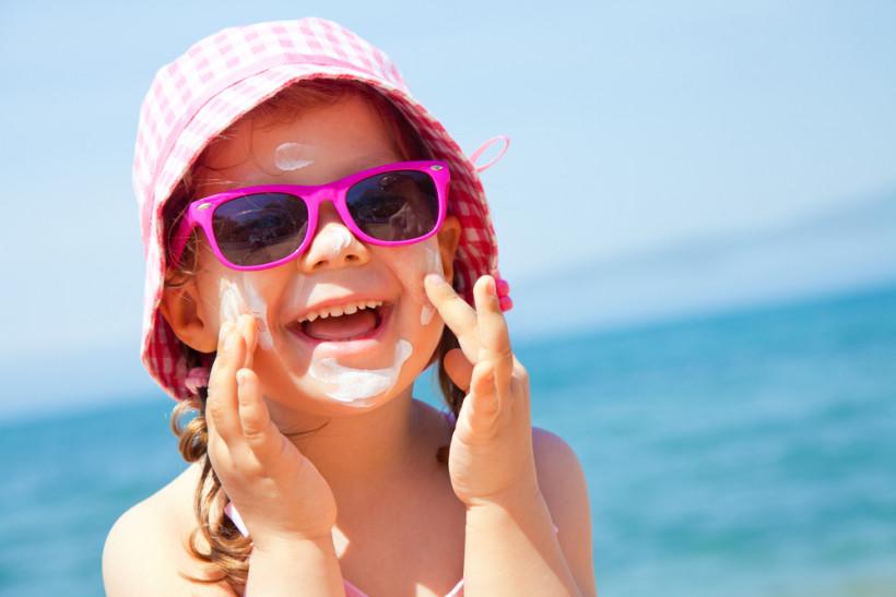 Девочка на пляже с солнцезащитным кремом