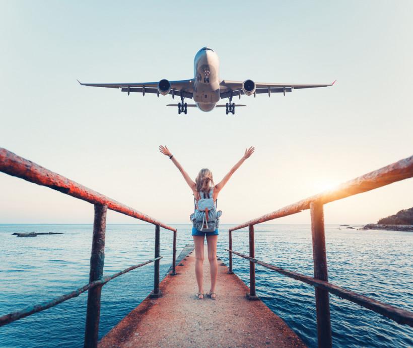 В отпуск - женщина машет руками самолету