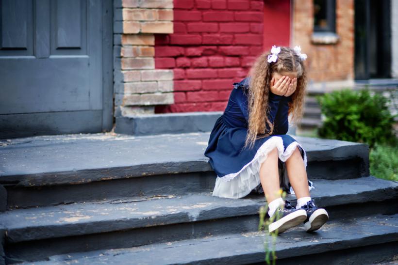 Булінг у школі - дівчинка плаче на сходах біля входу