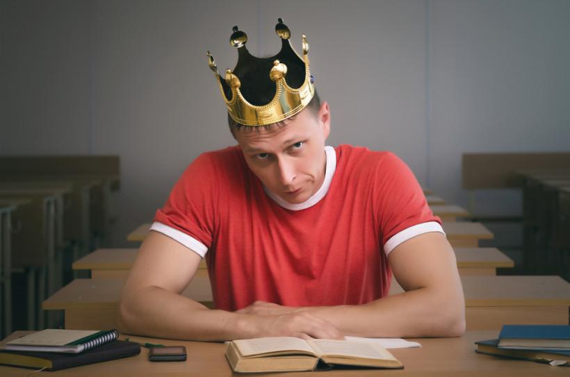 Мужчина за партой и в короне