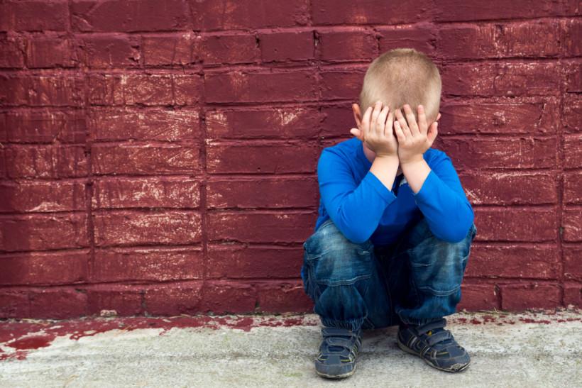 Ребенок сидит у стены и боится