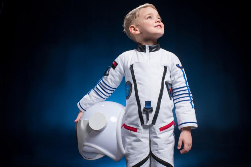 Мальчик космонавт на фоне темного неба