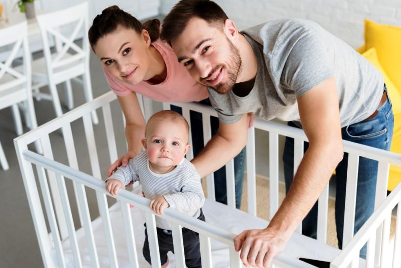 родители и малыш в кроватке