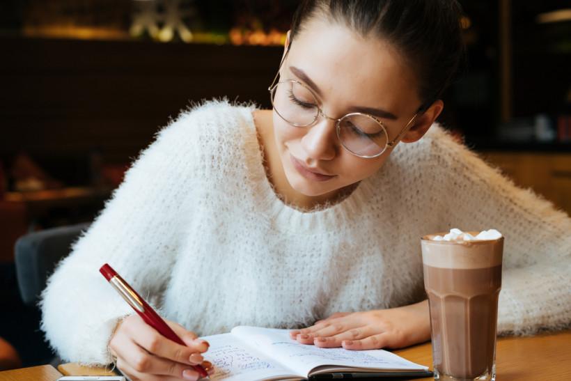 Женщина пишет в блокнот