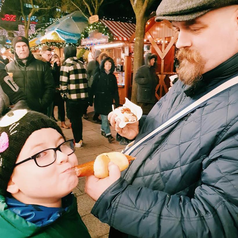 Мальчик ест традиционную сосиску в Берлине
