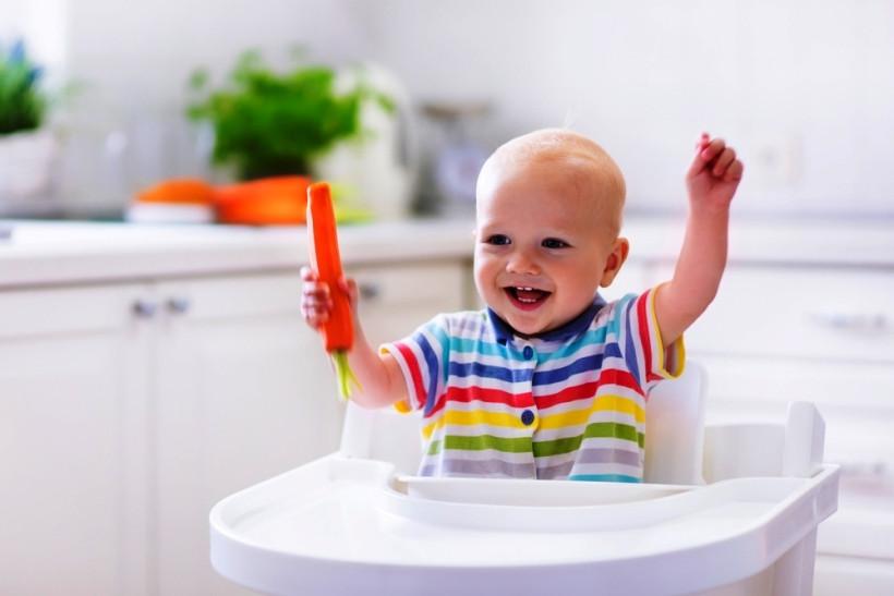 радостный малыш с морковкой