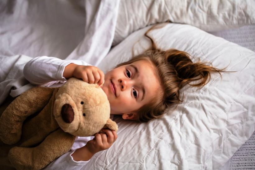 девочка в кровати с мишкой