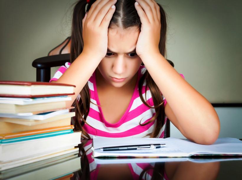 уставшая школьница за партой с книгами