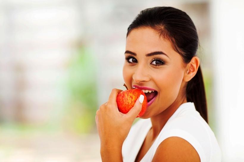 девушка ест яблоко во время разгрузочного дня