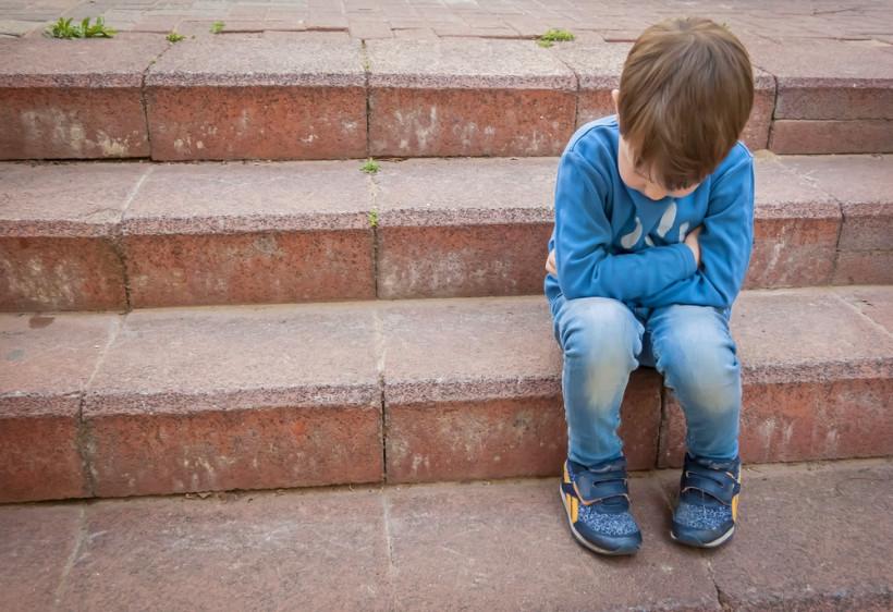 Наказанный ребенок сидит на ступеньках - насилие над ребенком