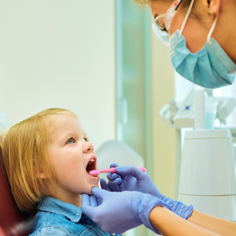 Стоматолог чистит зубки ребенку - ранний кариес