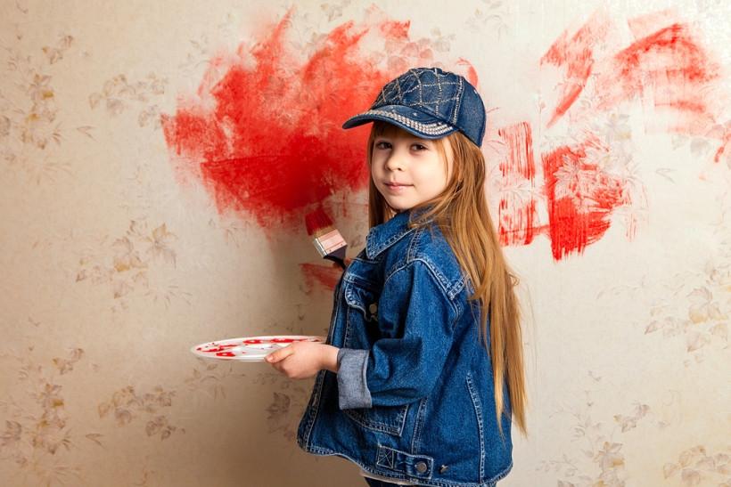 дівчинка малює на стіні