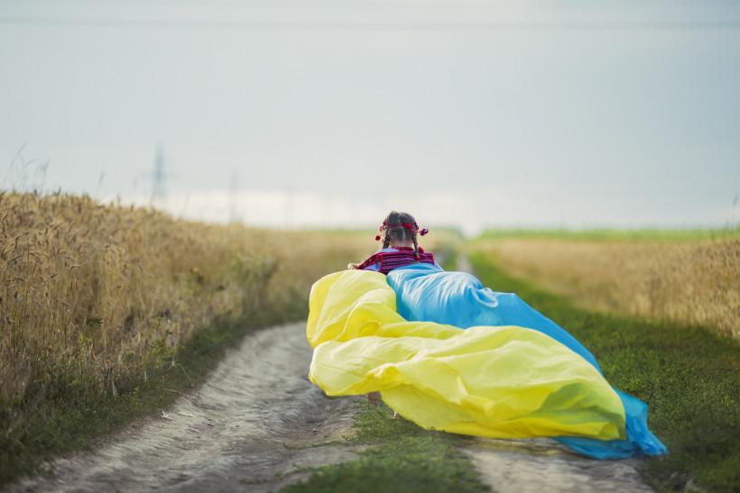 Ребенок с украинским флагом бежит в поле