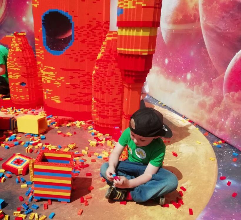 ребенок собирает лего на фестивале робототехнки