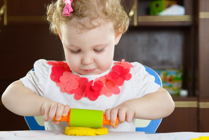 девочка лепит из цветного теста