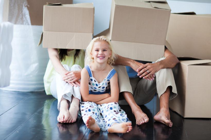 Смеющаяся девочка на фоне родителей в коробке