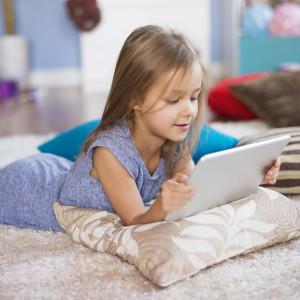 Дівчинка лежить із планшетом