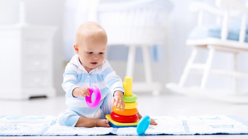 Малыш играет на коврике