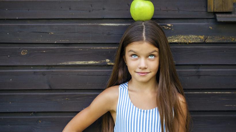 Девочка -подросток с яблоком на голове