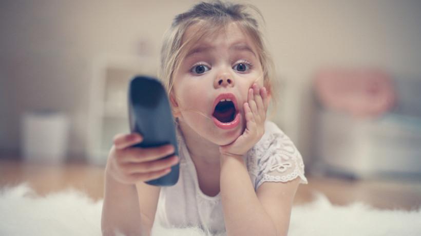 Дівчинка дивиться телевізор